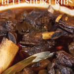 pot of red wine braised beef short ribs cooking with herbs and sauce