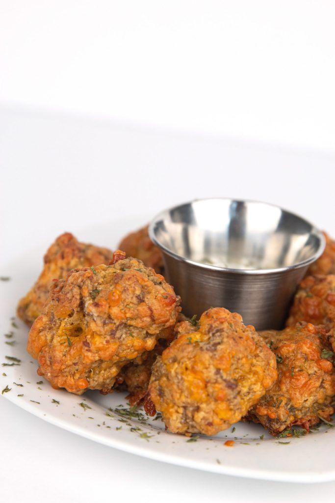 white plate of jalapeno sausage balls with a metal mini cup of ranch dressing sprinkled with dried parsely