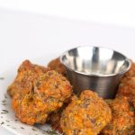 white plate of jalapeno cheddar sausage balls with sprinkles of prasely and a cup of ranch dressing