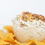 glass bowl of easy cheddar bacon ranch dip with cheese and bacon on top with chips around the bowl