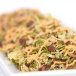 white plate of shaved brussels sprouts with spicy mayo drizzled on top