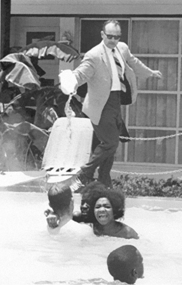 Hotel owner pouring acid in the pool while black people swim in it, ca. 1964.