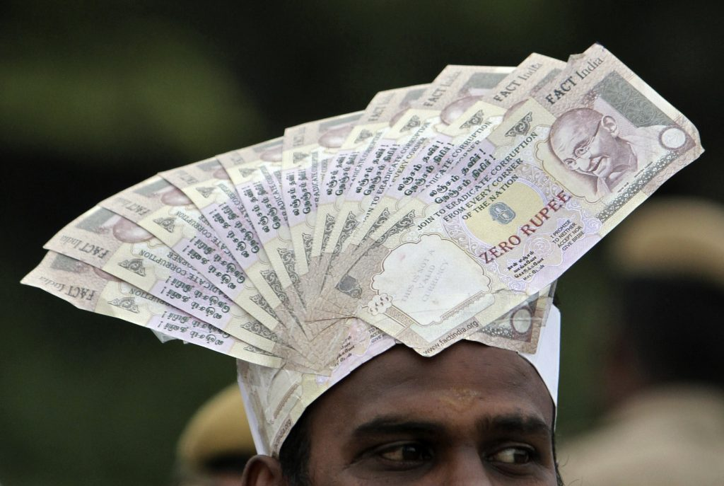 A supporter of veteran Indian social activist Anna Hazare wears a cap lined with fake currency notes while attending a public meeting by Hazare in the southern Indian city of Chennai December 18, 2011. Hazare, while addressing a public meeting on Sunday, said he was firm on his plan for an indefinite fast later this month if the government did not bring an effective anti-graft legislation in Parliament. REUTERS/Babu