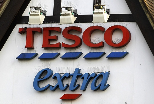 A Tesco supermarket sign in London. Photo Credit: Sang Tan/ AP