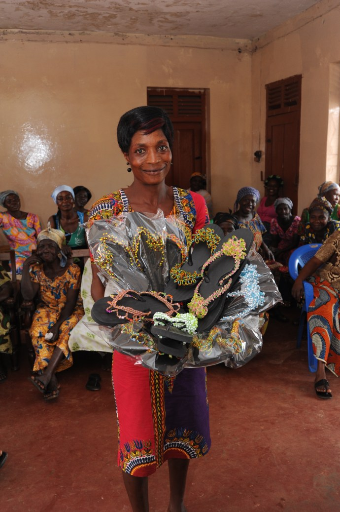 Woman holds her newly made beaded sandals