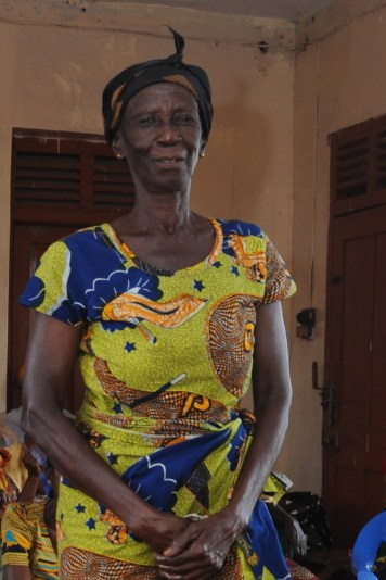 beneficiary smiling and standing in front of the camera