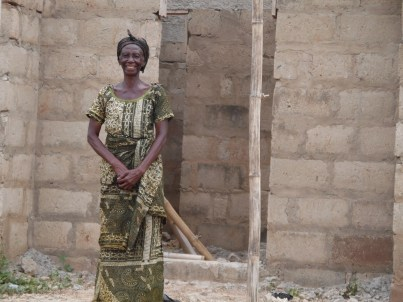 beneficiary standing in front of her home