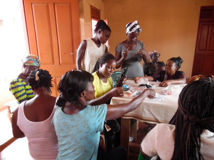 a group of women observes beads and learns to make beaded products