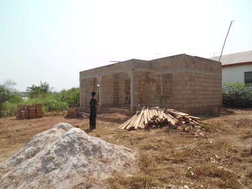 beneficiary of the program in front of her new home with the newly purchased wood