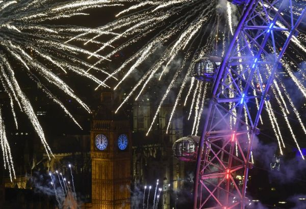 Fireworks explode around the London Eye wheel, the Big Ben clock tower and the Houses of Parliament to mark the beginning of the New Year in London, Britain, January 1, 2016. REUTERS/Toby Melville