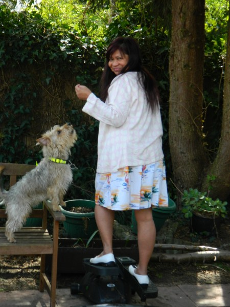 Jean on a portable elliptical machine in the garden with Diesel looking on