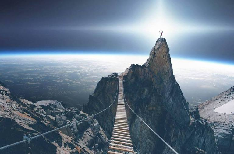 Hanging bridge leading to a mountain peak with a man standing triumphantly on the peak. A planet is seen in the background