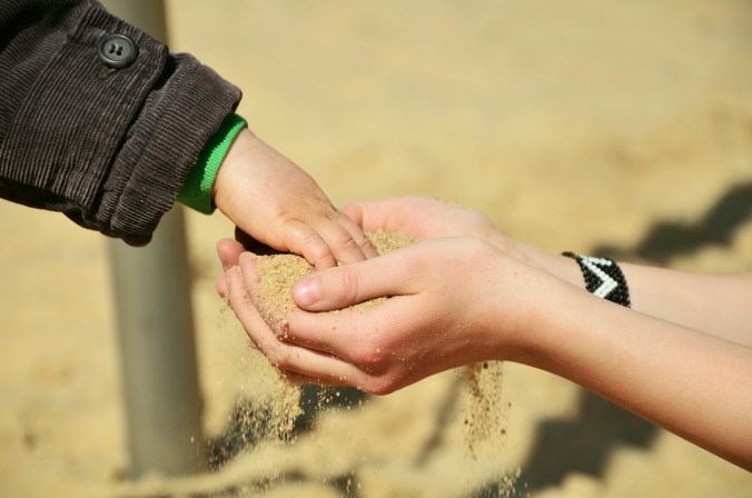 child puts hand in sand, which is in the hands og a grown up