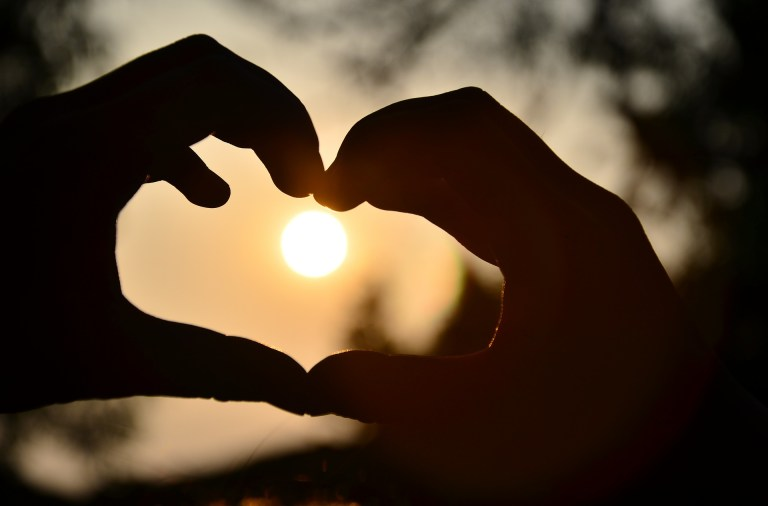 Hands make heart shape with the sun visible inside.