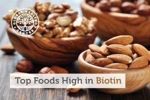 A table with organic mixed nuts. Biotin is an essential vitamin that is commonly found in foods such as nuts and vegetables.