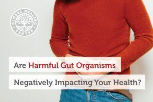A woman holding her abdomen. There are many types of harmful organisms that can negatively affect your health.