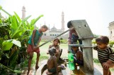 Children getting a bath at a water pump in India.