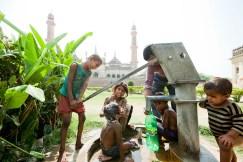 Children getting a bath at a water pump in India.