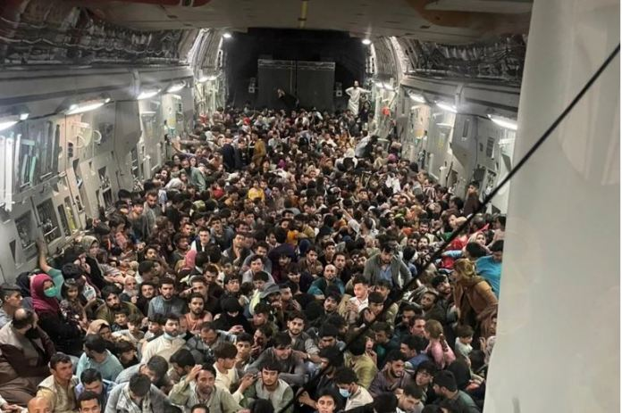 Evacuees crowd the interior of a US Air Force C-17 Globemaster III transport aircraft, carrying some 640 Afghans to Qatar from Kabul. [Handout/Defense One via Reuters]