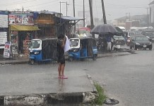 Young Lady Stages EndSARS Protest Under The Rain In Warri