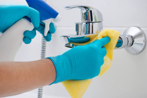 gloved hands cleaning a faucet