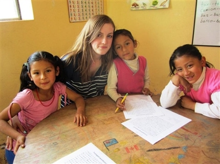 volunteer assisting children with their work at Picaflor House