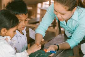 Cambodian teacher helping the kids