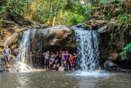 Group of volunteer swimming in the waterfall