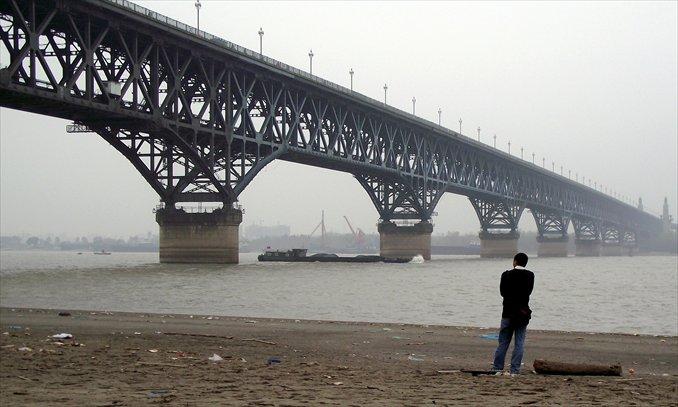 A man watches the Nanjing Yangtze River Bridge from a bank in Nanjing, Jiangsu Province. Photo: IC
