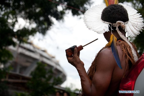 An indigenous man gazes at Maracana Stadium at the old Indian Museum in Rio de Janeiro, Brazil, Jan. 16, 2013. The government of Rio de Janeiro plans to tear down an old Indian museum beside Maracana Stadium to build parking lot and shopping center here for the upcoming Brazil 2014 FIFA World Cup. The plan met with protest from the indigenous groups. Now Indians from 17 tribes around Brazil settle down in the old building, appealing for the protection of the century-old museum, the oldest Indian museum in Latin America. They hope the government could help renovate it and make part of it a college for indigenous Indians. (Xinhua/Weng Xinyang)