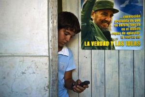 Cuban boy looking at his mobile phone. Image courtesy of Huffington Post