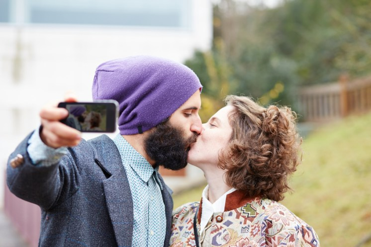 Couple taking a photograph of themselves kissing with a smartphone