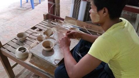 Ein Künstler bei der Produktion einer Bambusschüssel. An seiner Wange die für das Land typische Paste des Thanaka-Baumes.