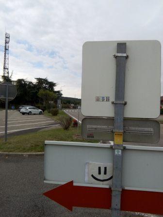Spot d'auto-stop avec pancarte sourire et un sticker d'Hitchwiki
