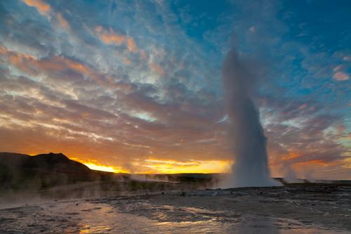 Geyser erupting at Geysir before sunrise in Iceland