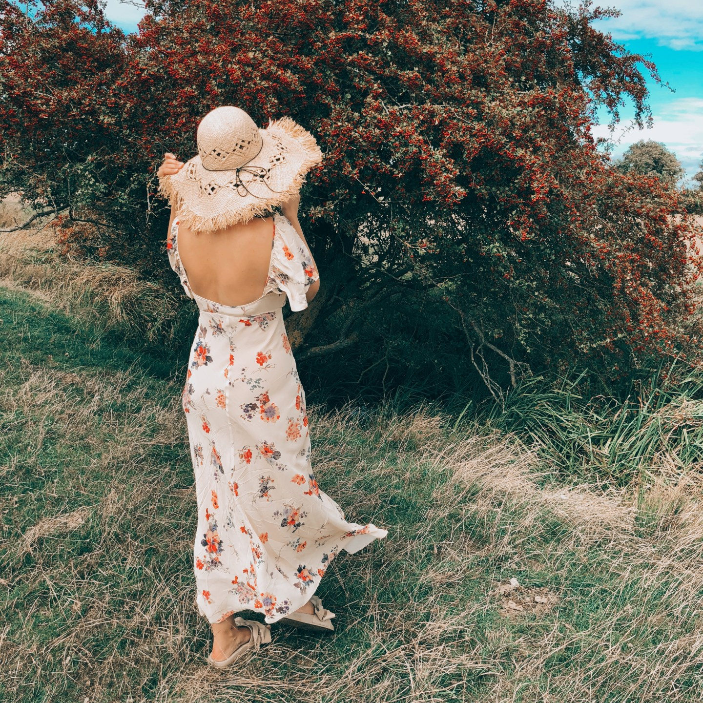 UK STAYCATION IDEAS: a girl in a rural landscape wearing a long summer dress and a straw hat