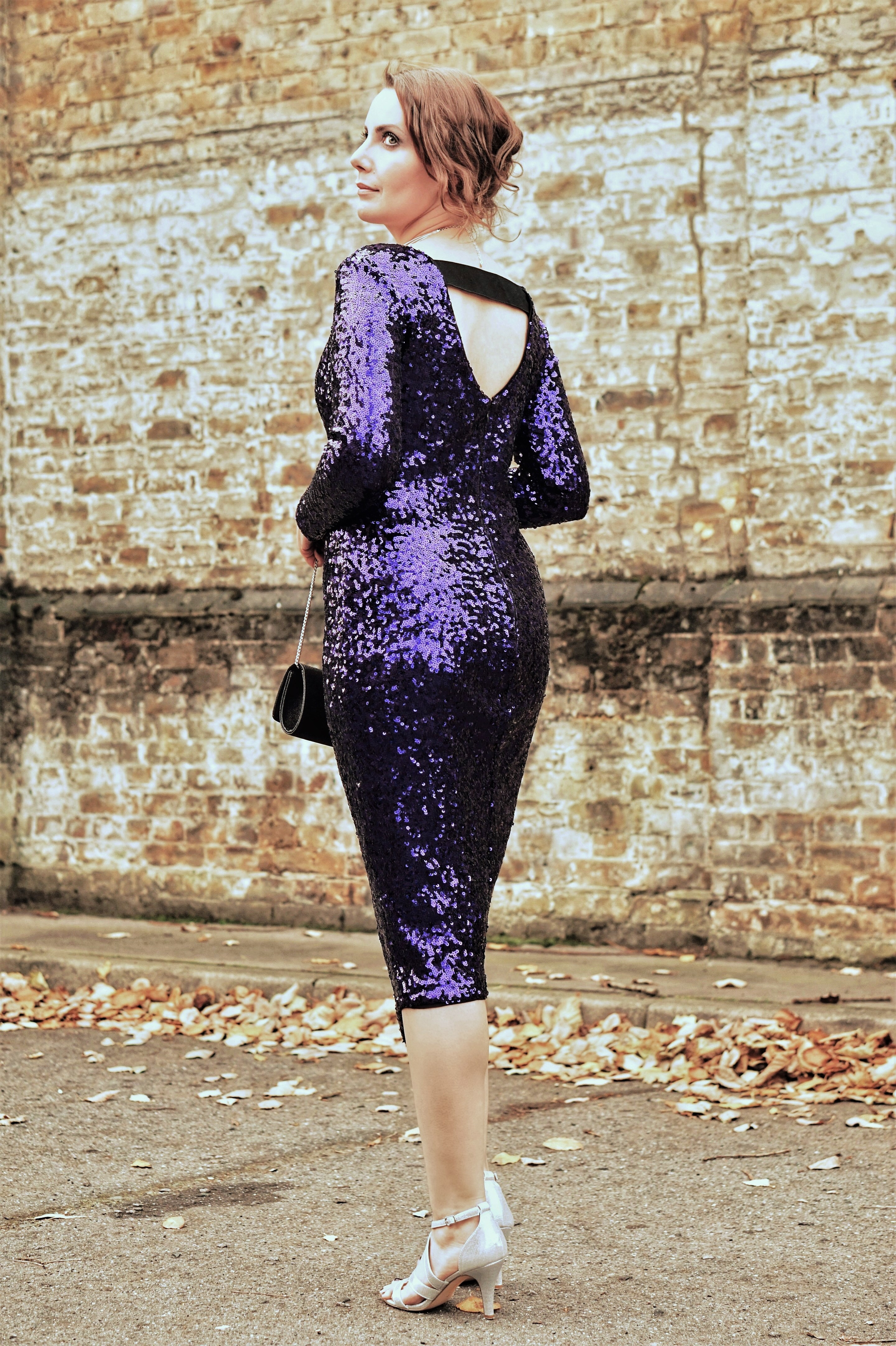 Style inspiration: purple sequin long sleeve midi length party dress, silver shoes, leaf ear climber, clutch bag.