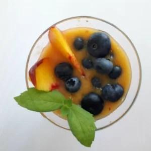 Koktajl owocowy, udekorowany borówkami, plasterkiem brzoskwini i listkiem mięty
