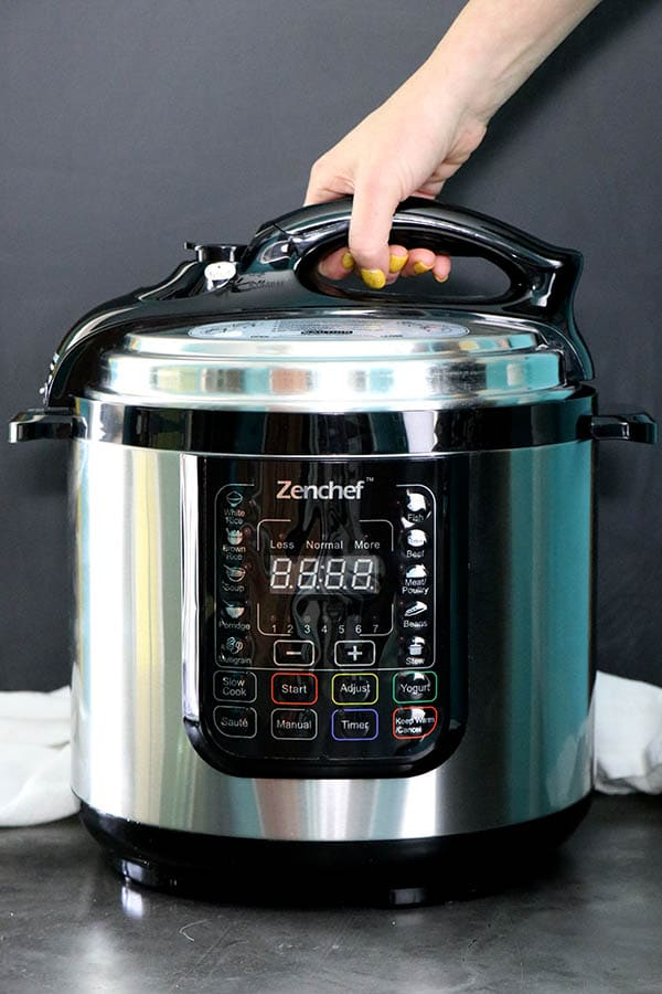 Hand opening a ZenChef Multipurpose Pressure Cooker