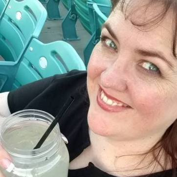Color photo of Gluten Gourmet Amy drinking a hard lemonade at a concert.
