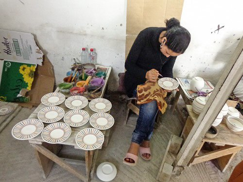 Woman hand-painting plates at the ceramic co-op.