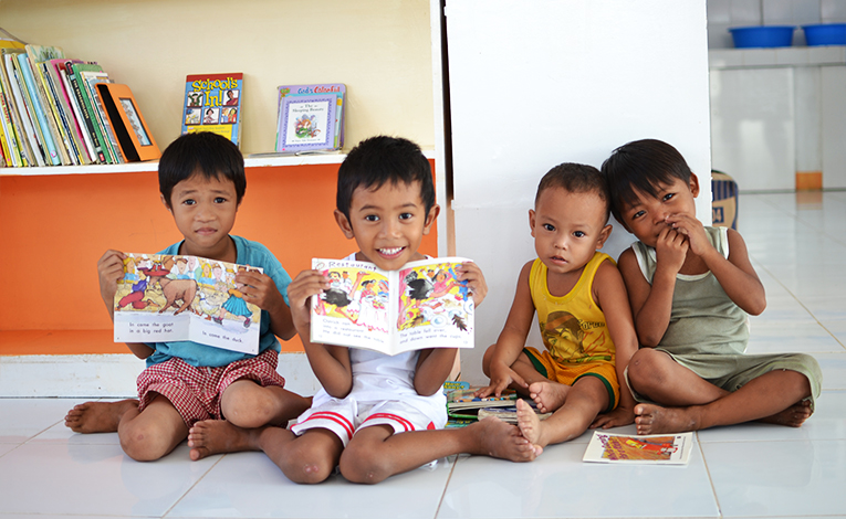 Young Filipino boys holding books