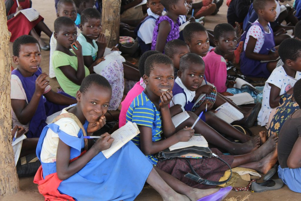 Children sitting with notepads and pens at school