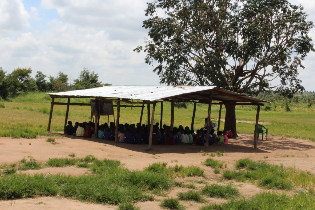 Kids attending school under a tin roof at a distance