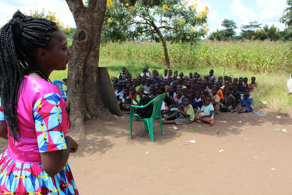 Children sitting under a tree being instructed during class