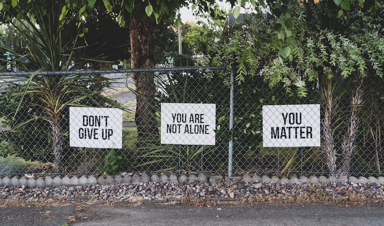 uplifting signs posted along a fence