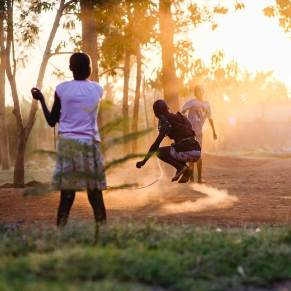 Girls playing jump rope at sunset in Kenya