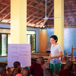 Volunteer teaching a class of young monks