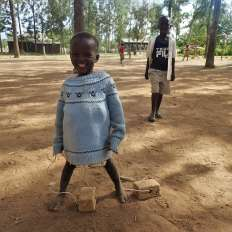 Little girl smiling and playing in Kenya