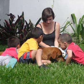 Volunteer teacher and students laying in the grass with a dog